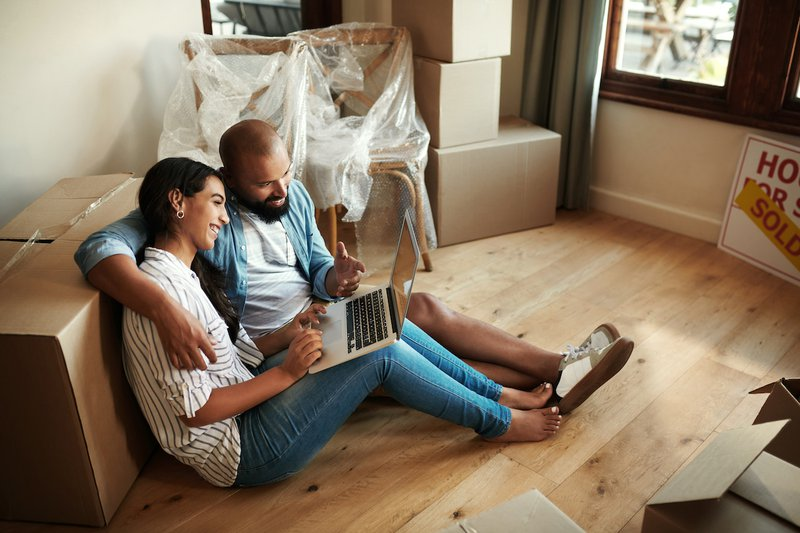 Shot of a young smiling couple sitting on the floor surrounded by moving boxes while they use a laptop